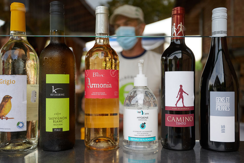 6 Flaschen, 5 davon Weinflaschen, dazwischen eine mit Desinfektionsmittel